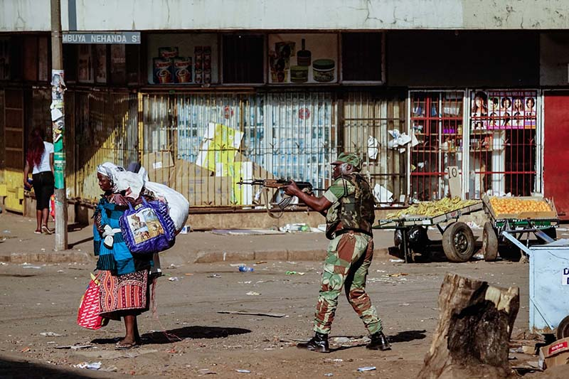 A vendor walks away with her wares as soldiers disperse demonstrators on August 1, 2018 during a demonstration demanding results of a general election in Harare Zimbabwe.